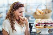 Astonished pretty woman looking at cakes — Stock Photo