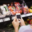 Woman reading her shopping list on smartphone — Stock Photo #81863164