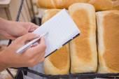 Alışveriş listesini ekmek somun yukarıda yazılı bir kadın — Stok fotoğraf