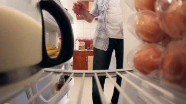 Man looks in the fridge to get milk — Vídeo Stock