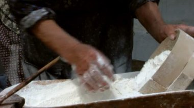 Old woman sifting flour through a sieve in a wooden bowl — Stock Video