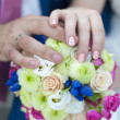 Hands with wedding rings and beautiful fresh wedding bouquet — Stock Photo #62092427