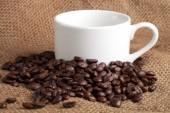 Leere tasse und gerösteten kaffeebohnen auf sackleinen — Stockfoto