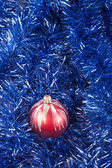 Red Christmas ball on the background of blue tinsel  — Stock Photo