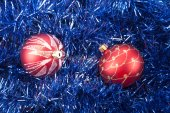 Red Christmas balls on the background of blue tinsel — Stock Photo