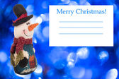 Knitted snowman with a card on a background of blue Christmas — Stock Photo