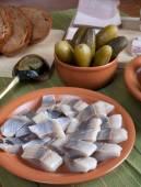 Ringa balığı, ekmek, turşu ve pastırma yeşil peçeteye plakalı — Stok fotoğraf