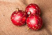 Three red Christmas tree ball on sacking — Stock Photo