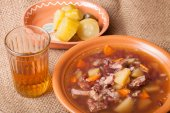 Soup with bean and potato, salty cucumbers and moonshine on a sa — Stock Photo