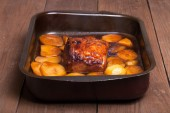 Piece of pork and potatoes in the pan for roasting on an old woo — Stock Photo