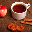 Cup of tea on old wooden table with  red apple, dried apricots a — Stock Photo #55605331