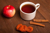 Cup of tea on old wooden table with  red apple, dried apricots a — Stock Photo