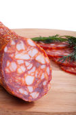 Chorizo sausage with herbs and pepper on the board — Stock Photo