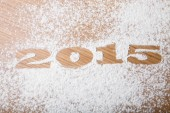 2015 with flour on the table of the bakery — Stock Photo