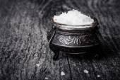 Sea salt in a large antique salt shaker on old wooden tabl — Stock Photo
