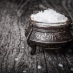 Sea salt in a large antique salt shaker on old wooden tabl — Stock Photo #57935621