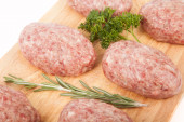 Fresh uncooked patties on a wooden board with rosemary and parsl — Foto de Stock