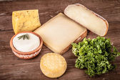 Various types of cheese on a wooden background with parsley.Tint — Stockfoto