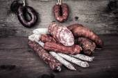 Several types of sausages on a wooden background — Stock Photo