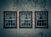 Three windows on the shabby wall closed with curtains — Stock Photo
