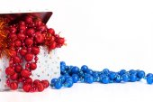 Tin box with blue and red beads and tinsel on a white background — Stock Photo
