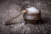 Sea salt in an old utensils and a small spoon on a wooden table — Stock Photo