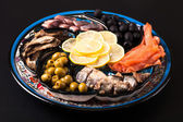 Assorted fish on a plate on a dark background. — Stock Photo