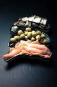 Fish assortment and olives on a plate on a dark background. With — Stock Photo
