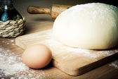 Dough on a board with flour. olive oil, eggs, rolling pin — Stock fotografie