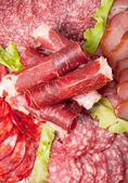 Slices of different kinds of meat with green salad — Stock Photo