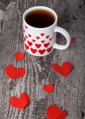 Valentine hearts and cup of tea on the old wooden table — Photo