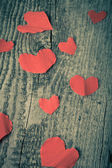 Many Valentine hearts on the old wooden table. Toned — Stock Photo