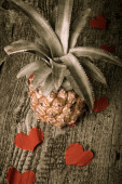 Many Valentine hearts with ananas on the old wooden table. Toned — Stock Photo