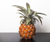 Fresh whole pineapple on a black table near white wall — Stock Photo