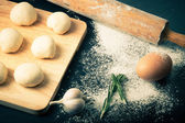 Garlic, rosmary, egg, rolling pin and pieces of dough on the woo — Stock Photo