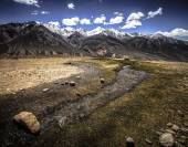 The rapid stream in the valley and snow-capped peaks of the moun — Stockfoto