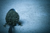 Spoon with dried herb and salt on the stone background. Toned — ストック写真