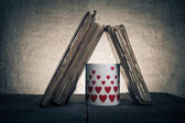 Old books and mug with many pictured hearts on the old wooden ta — Stockfoto