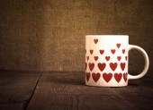 Mug with many pictured hearts on the old wooden table. Toned — Stockfoto