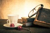 Cup of coffee, shokolad, glasses and stack of old books on the o — Stockfoto