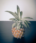 Fresh whole pineapple on a black table near white wall. Toned — Stock Photo