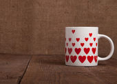 Mug with many pictured hearts on the old wooden table — Stock Photo