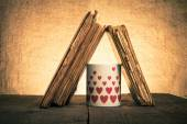 Old books and mug with many pictured hearts on the old wooden ta — Stock Photo