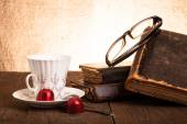 Cup of coffee, shokolad, glasses and stack of old books on the o — Stock Photo