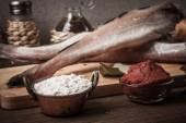 Fresh fish, vegetables, flour, tomatoe paste and spices on a woo — Stock Photo