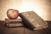 Still life with apple and a stack of old books on old wooden tab — Stockfoto