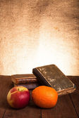 Still life with apple, orange and a stack of old books on old wo — Stockfoto