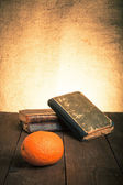 Still life with orange and a stack of old books on old wooden ta — Stockfoto