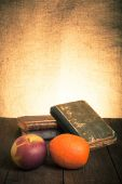 Still life with apple, orange and a stack of old books on old wo — Stok fotoğraf