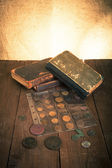Vintage books and coins on old wooden table. Toned — Foto de Stock